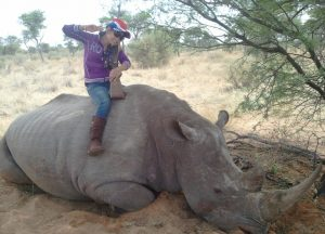 A prostitute poses with a rhino on Steyl's reserve. Credit: Freeland.org