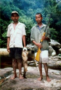 Two bushmeat poachers holding a White-fronted Brown Lemur, northeast Madagascar. (CCA-SA3.0)
